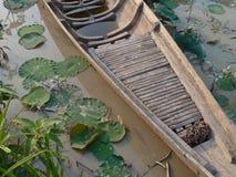 Barco asiático de madera de la canoa en Lily Pond Fotos de archivo