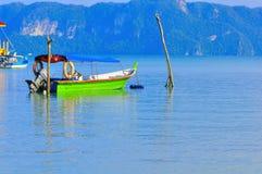 Barco atado a dos polos de madera en la isla de Langkawi Imagenes de archivo