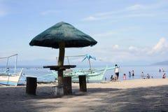 Barco atrás do parasol na praia branca da areia Imagem de Stock Royalty Free