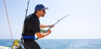 Barco azul de la pesca en alta mar del mar con el pescador Foto de archivo