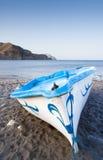 Barco azul del barco en una playa Foto de archivo libre de regalías
