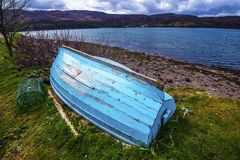 Barco azul en el lago Shieldaig en las montañas de Escocia imágenes de archivo libres de regalías