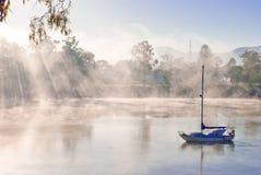 Barco azul en un río brumoso Foto de archivo