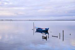 Barco azul no meio do lago imagens de stock