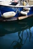 Barco azul viejo con los flotadores y las reflexiones Fotos de archivo
