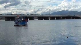Barco azul vietnamita en el ancla en el río pescadores que lanzan redes de pesca en el barco en el fondo hay wi de un puente almacen de video