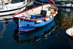 Barco azul y anaranjado con reflexiones Foto de archivo libre de regalías