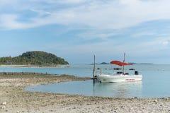 Barco blanco en la orilla en el fondo de la isla y del cielo azul Foto de archivo