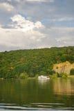 Barco blanco que flota rio abajo en un fondo del bosque Imagenes de archivo