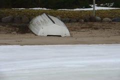 Barco branco na praia na costa de um lago congelado foto de stock
