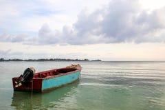 Barco cerca de la orilla con las nubes y agua tranquila del claro Foto de archivo libre de regalías