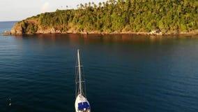 Barco cerca de la orilla tropical Opinión del abejón que sorprende de la navegación de lujo blanca moderna del yate en la agua de almacen de metraje de vídeo