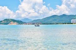 Barco coberto de vegetação e só da montanha no mar Foto de Stock