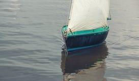 Barco com as velas brancas que flutuam no fim da água acima Imagem de Stock