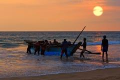 Barco com os fishers no fundo do por do sol Imagem de Stock Royalty Free