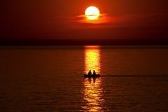 Barco com povos de encontro a um por do sol alaranjado Foto de Stock