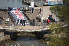 Barco con el modelo del Union Jack en el tejado que celebra la boda real que pasa debajo del puente Foto de archivo libre de regalías