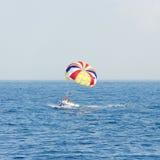 Barco con el paracaídas colorido que flota en el mar Foto de archivo libre de regalías