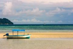 Barco con el toldo en la playa fotografía de archivo