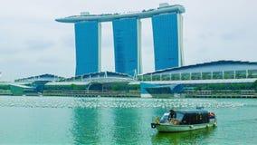 Barco con la bahía cruzada del puerto deportivo de los turistas con el edificio de Marina Bays Sands en fondo Fotografía de archivo libre de regalías