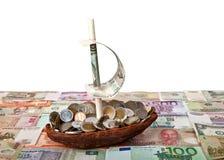 Barco con las monedas en el fondo de billetes de banco de los países diferentes Fotografía de archivo libre de regalías