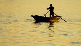 Barco con un hombre en el fondo del mar en la puesta del sol Imagen de archivo libre de regalías