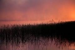 Barco con un par en él en el lago en la niebla fotos de archivo