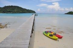 Barco da canoa e porto de madeira pelo mar Fotos de Stock