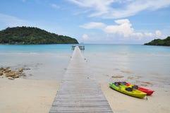 Barco da canoa e porto de madeira pelo mar Fotografia de Stock