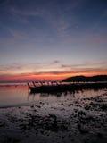 Barco da cauda longa ancorado na costa pelo alvorecer com o céu bonito e a lua imagem de stock
