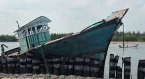 Barco danificado do pescador em um porto pequeno indiano fotografia de stock royalty free