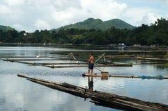 Barco de bambú de la balsa del cuerpo de la paleta masiva del barquero a través del lago de la montaña imagen de archivo