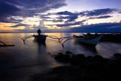 Barco de Banca en la puesta del sol en la playa Fotos de archivo libres de regalías
