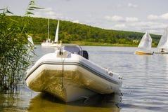 Barco de borracha com o motor na costa arenosa do reservatório imagem de stock royalty free