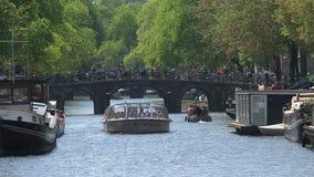 Barco de canal con un puente típico en el fondo en Amsterdam almacen de metraje de vídeo
