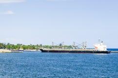 Barco de carga que llega la entrada del puerto de Santo Domingo, República Dominicana con un mar azul tropical fotos de archivo