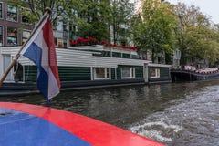 Barco de casa del canal con la bandera holandesa Imagen de archivo