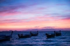 barco de cola larga en el mar Cielo azul y clound anaranjado Fotos de archivo