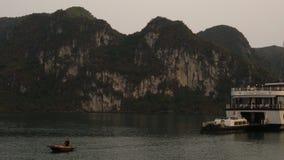 Barco de cruceros amarrado y barco de rowing en la puesta del sol en la bahía larga de la ha, Vietnam almacen de video