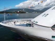 Barco de cruceros atracado con el mar y las montañas Imagen de archivo