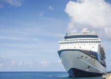 Barco de cruceros azul y blanco bajo las nubes hinchadas Imagenes de archivo