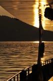 Barco de cruceros en el lago en la puesta del sol Foto de archivo libre de regalías