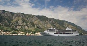 Barco de cruceros en la bahía contra el contexto de las montañas fotos de archivo