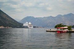 Barco de cruceros en la bahía entre las montañas, el barco del taxi en el embarcadero en el primero plano imagen de archivo