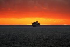 Barco de cruceros en la puesta del sol en el océano Imágenes de archivo libres de regalías