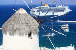 Barco de cruceros enorme y un molino de viento en mykonos Foto de archivo libre de regalías