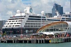 Barco de cruceros fuera de la nube en el muelle del Queens en el waterf de Auckland Imágenes de archivo libres de regalías