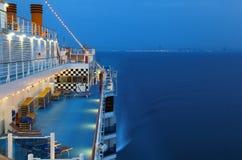 Barco de cruceros iluminado con la gente en el mar Foto de archivo