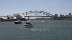 Barco de cruceros privado grande en Sydney con el puente del teatro de la ópera y del puerto en el fondo almacen de metraje de vídeo