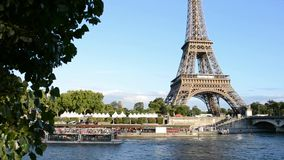 Barco de cruceros que mueve encendido río Sena cerca de la torre Eiffel en París metrajes